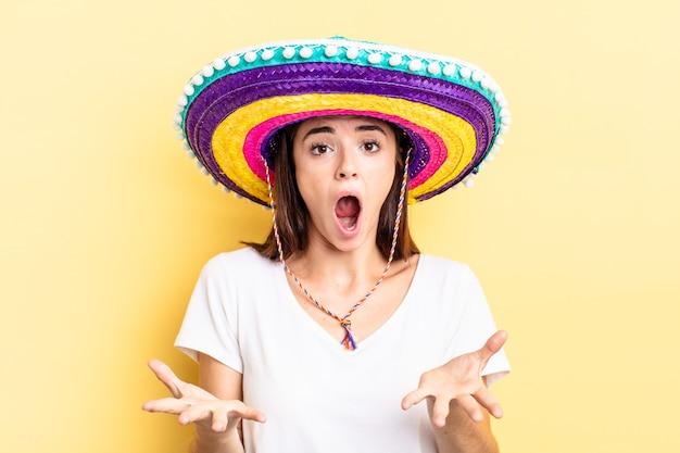 Joven hispana que se siente extremadamente conmocionada y sorprendida. concepto de sombrero mexicano