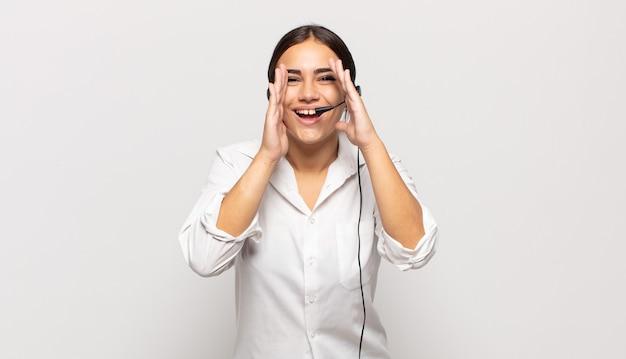 Joven hispana que se siente feliz, emocionada y positiva, dando un gran grito con las manos al lado de la boca, gritando