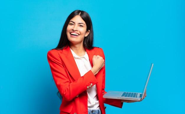 Joven hispana que se siente feliz, positiva y exitosa, motivada ante un desafío o celebrando buenos resultados. concepto de laptop