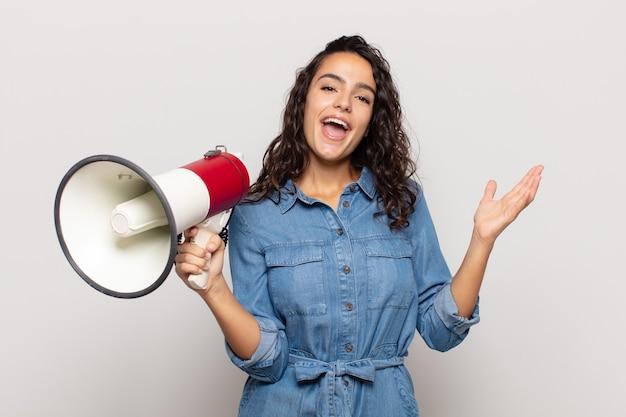 Joven hispana que se siente feliz, sorprendida y alegre, sonriendo con actitud positiva, dándose cuenta de una solución o idea