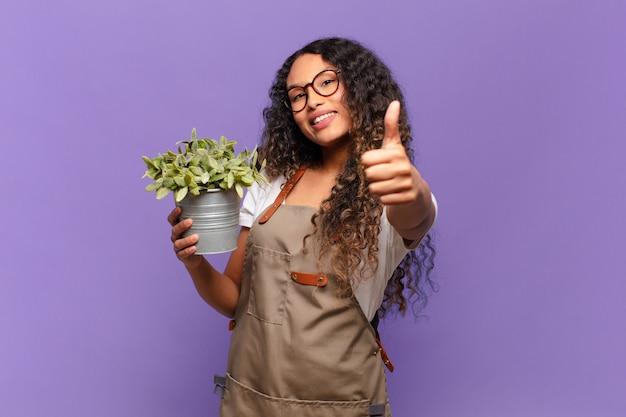 Joven hispana que se siente orgullosa, despreocupada, segura y feliz, sonriendo positivamente con los pulgares hacia arriba. concepto de cuidador de jardín