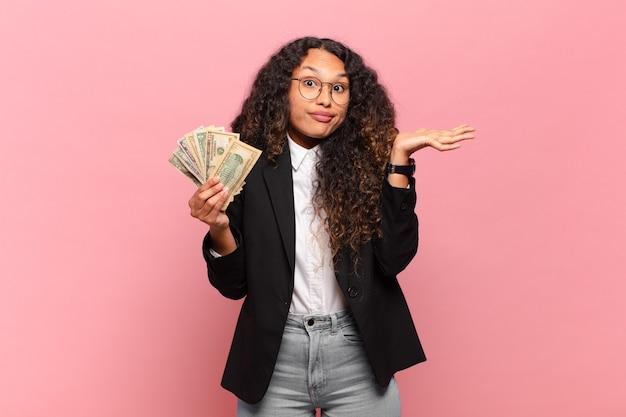 Joven hispana que se siente perpleja y confundida, dudando, ponderando o eligiendo diferentes opciones con expresión divertida. concepto de billetes de dólar