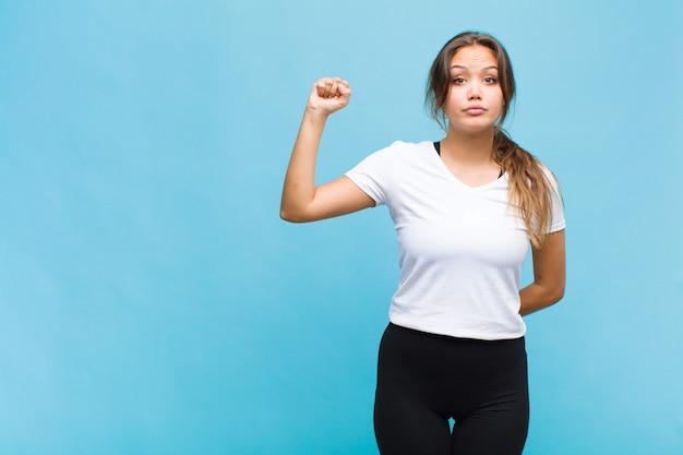 Joven hispana que se siente seria, fuerte y rebelde, levantando el puño, protestando o luchando por la revolución