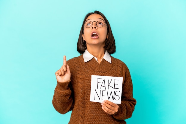 Joven hispana de raza mixta sosteniendo un cartel de noticias falsas apuntando hacia arriba con la boca abierta.