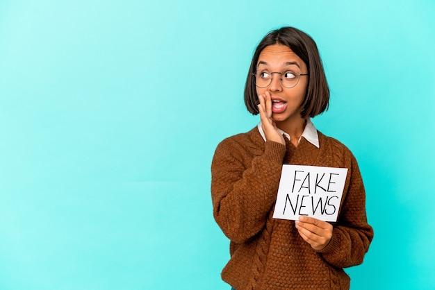 Joven hispana de raza mixta sosteniendo un cartel de noticias falsas está diciendo una noticia secreta de frenado en caliente y mirando a un lado
