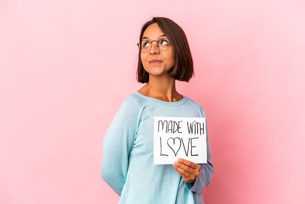Joven hispana de raza mixta sosteniendo un cartel de papel hecho con amor soñando con lograr metas y propósitos