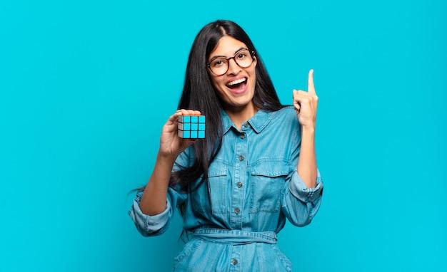 Joven hispana sintiéndose como un genio feliz y emocionado después de realizar una idea, levantando alegremente el dedo, ¡eureka !. concepto de problema de inteligencia