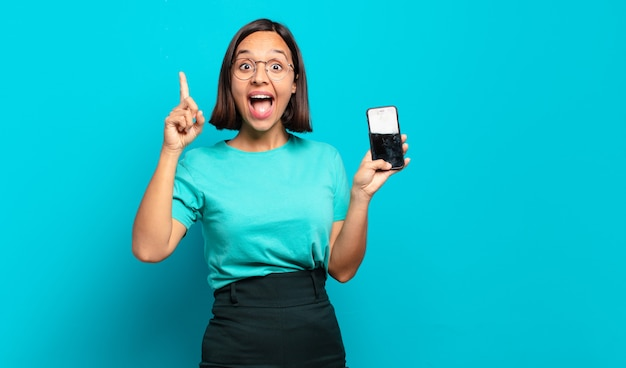 Joven hispana sintiéndose como un genio feliz y emocionado después de realizar una idea, levantando alegremente el dedo, ¡eureka!