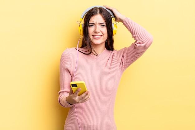 Joven hispana sintiéndose estresada, ansiosa o asustada, con las manos en la cabeza. concepto de auriculares y teléfono