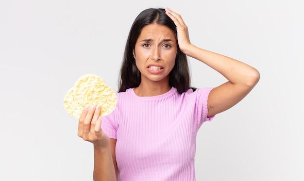 Joven hispana sintiéndose estresada, ansiosa o asustada, con las manos en la cabeza y sosteniendo una galleta de arroz. concepto de dieta