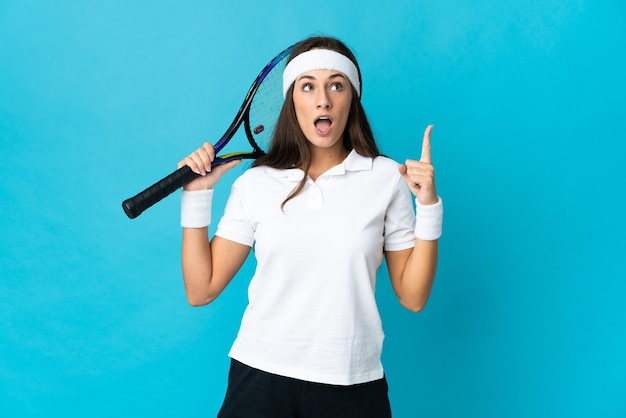 Joven hispana sobre azul aislado jugando al tenis y apuntando hacia arriba