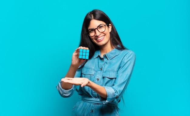 Joven hispana sonriendo alegremente, sintiéndose feliz y mostrando un concepto en el espacio de la copia con la palma de la mano. concepto de problema de inteligencia