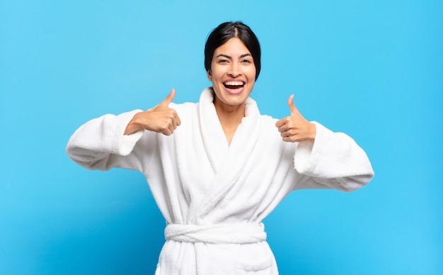 Joven hispana sonriendo ampliamente mirando feliz, positivo, seguro y exitoso, con ambos pulgares hacia arriba