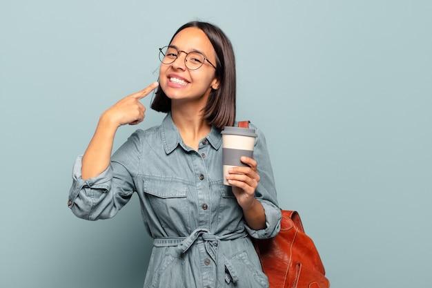 Joven hispana sonriendo con confianza apuntando a su propia sonrisa amplia, actitud positiva, relajada y satisfecha