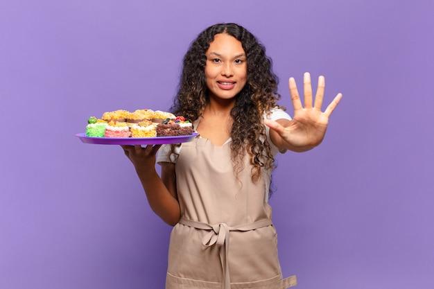 Joven hispana sonriendo y mirando amistosamente, mostrando el número cinco o quinto con la mano hacia adelante, contando hacia atrás. concepto de tortas de cocina