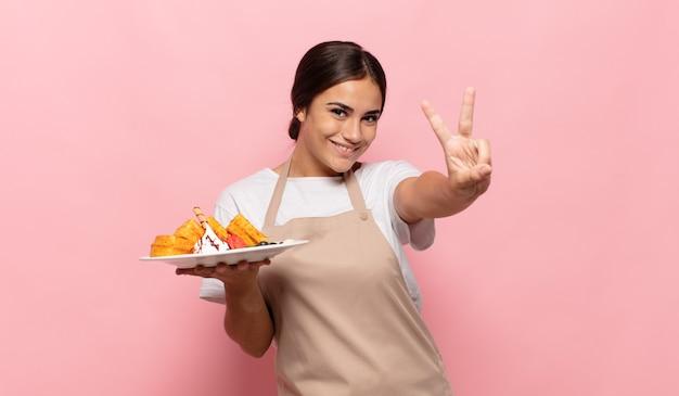 Joven hispana sonriendo y mirando amistosamente, mostrando el número dos o el segundo con la mano hacia adelante, contando hacia atrás