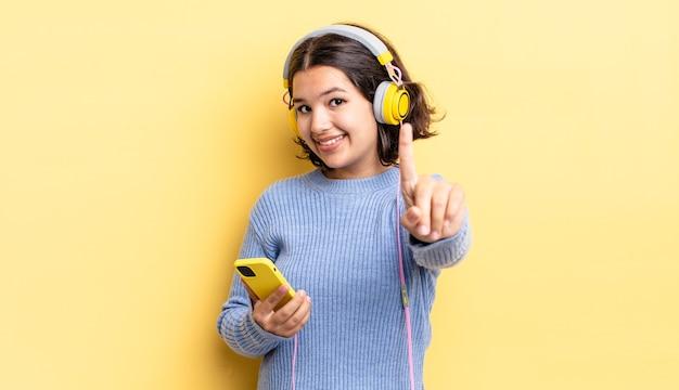 Joven hispana sonriendo con orgullo y confianza haciendo el número uno. concepto de auriculares y teléfono inteligente