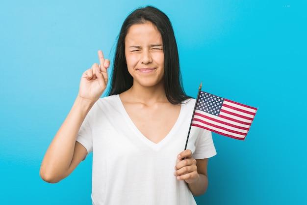 Joven hispana sosteniendo una bandera de estados unidos cruzando los dedos para tener suerte