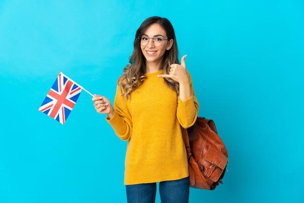 Joven hispana sosteniendo una bandera de reino unido en azul haciendo gesto de teléfono. llámame señal