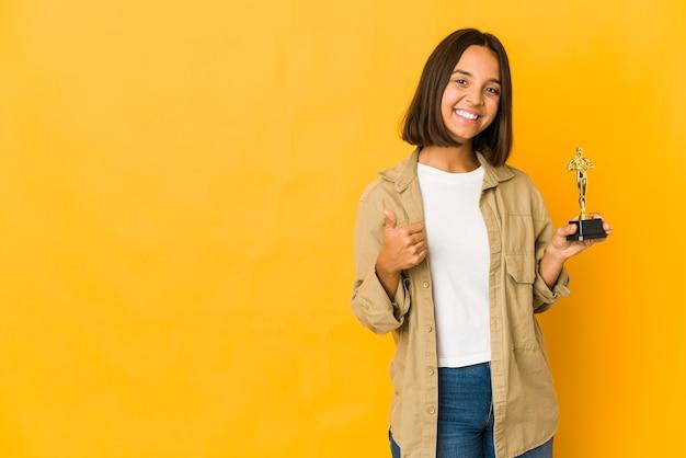 Joven hispana sosteniendo una estatuilla de premio sonriendo y levantando el pulgar hacia arriba