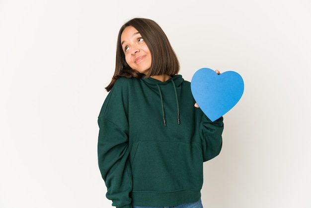 Joven hispana sosteniendo una forma de corazón soñando con lograr metas y propósitos