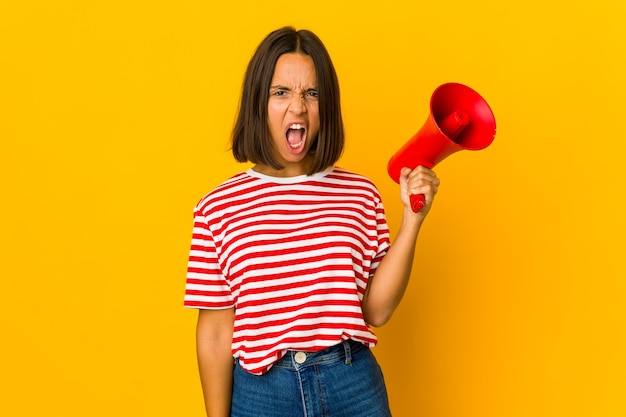Joven hispana sosteniendo un megáfono gritando muy enojado y agresivo.