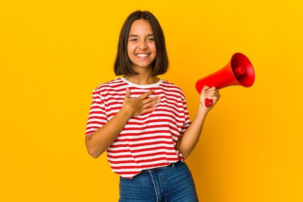 Joven hispana sosteniendo un megáfono se ríe a carcajadas manteniendo la mano en el pecho.