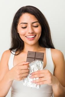 Joven hispana sosteniendo una tableta de chocolate