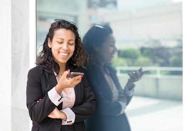 Joven hispana en traje formal con teléfono móvil sonriente al aire libre. espacio para texto.