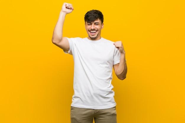 Joven hispano casual celebrando un día especial, salta y levanta los brazos con energía.