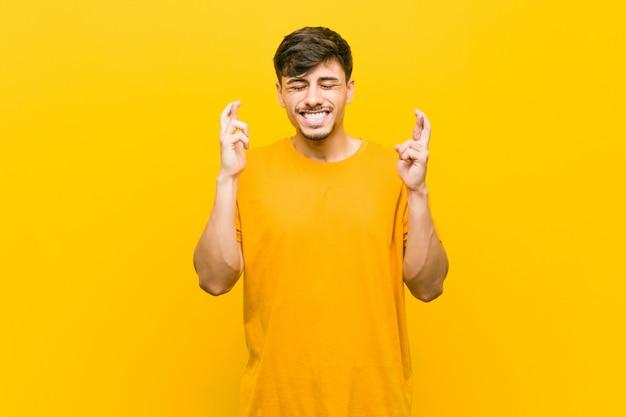 Joven hispano casual cruzando los dedos para tener suerte