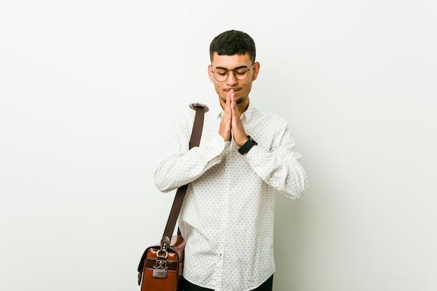 Joven hispano casual hombre de negocios tomados de la mano en rezar junto a la boca, se siente confiado.