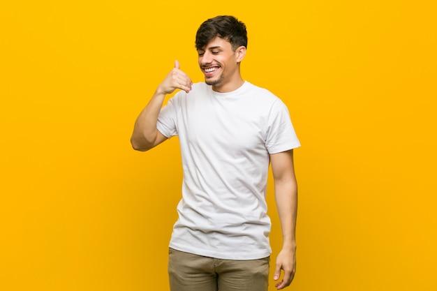 Joven hispano casual mostrando un gesto de llamada de teléfono móvil con los dedos.