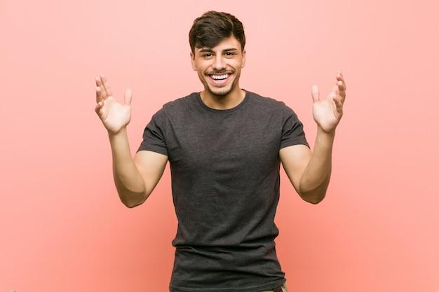 Joven hispano casual recibiendo una agradable sorpresa, emocionado y levantando las manos.