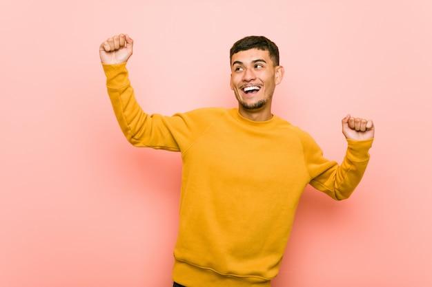 Joven hispano celebrando un día especial, salta y levanta los brazos con energía.