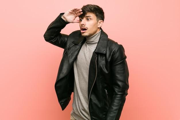 Joven hispano con una chaqueta de cuero mirando lejos manteniendo la mano en la frente.