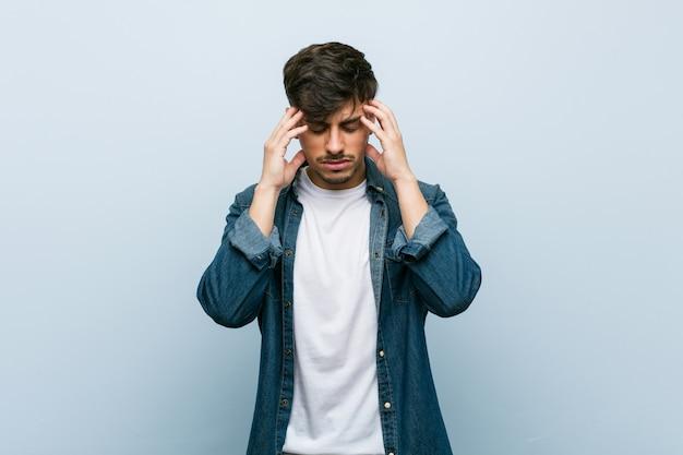 Joven hispano cool hombre tocar templos y tener dolor de cabeza.