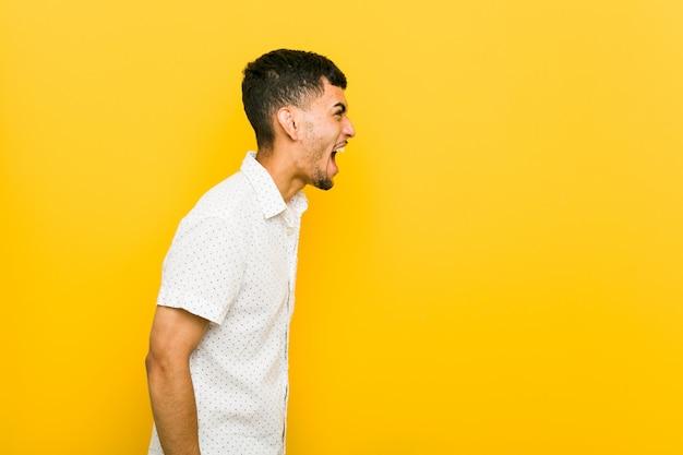 Joven hispano gritando hacia un espacio en blanco