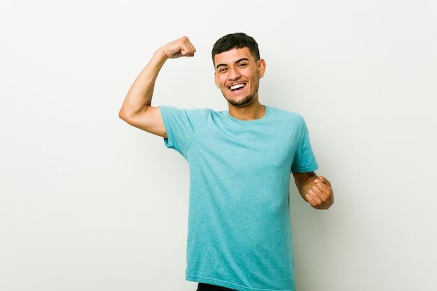 Joven hispano levantando el puño después de una victoria, concepto ganador.