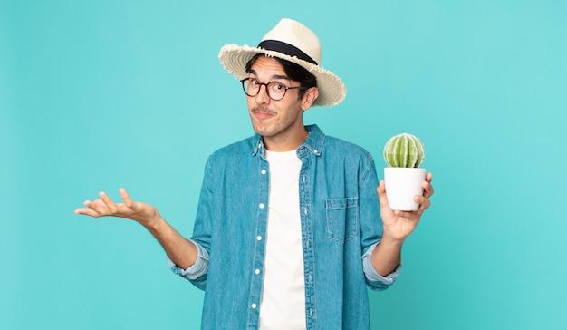 Joven hispano que se siente desconcertado y confundido y dudando y sosteniendo un cactus