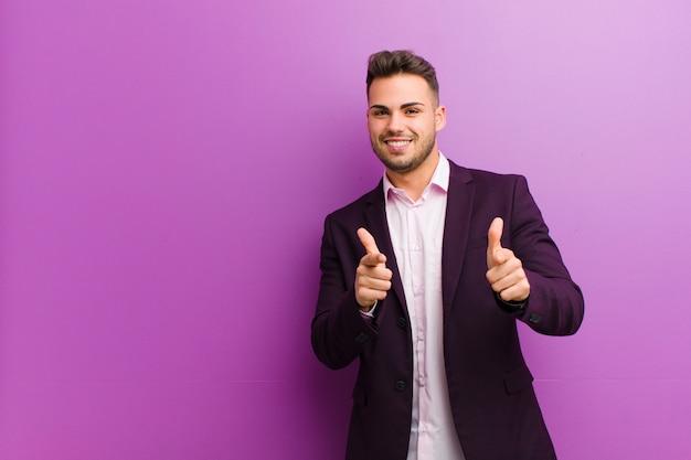 Joven hispano que se siente feliz, fresco, satisfecho, relajado y exitoso, apuntando a la cámara, eligiéndote