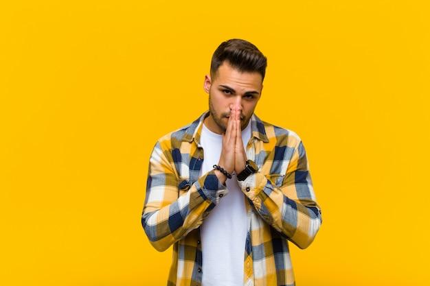 Joven hispano que se siente preocupado, esperanzado y religioso, rezando fielmente con las palmas presionadas, pidiendo perdón contra la pared naranja