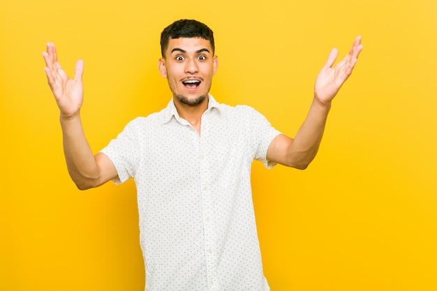 Joven hispano recibiendo una agradable sorpresa, emocionado y levantando las manos.