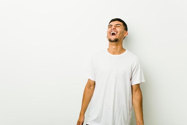 Joven hispano relajado y feliz riendo, cuello estirado mostrando los dientes.