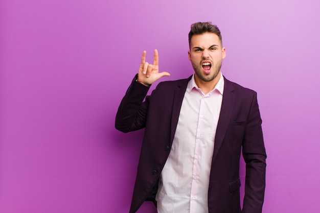 Joven hispano se siente feliz, divertido, confiado, positivo y rebelde, haciendo letrero de rock o heavy metal con la mano