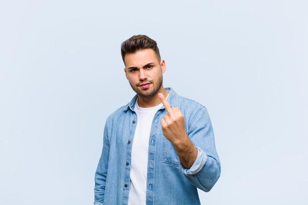 Joven hispano sintiéndose enojado, molesto, rebelde y agresivo, moviendo el dedo medio, luchando contra la pared azul