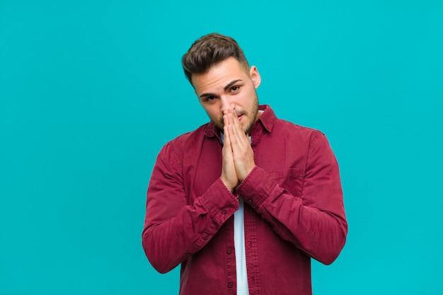 Joven hispano sintiéndose preocupado, esperanzado y religioso, rezando fielmente con las palmas presionadas, pidiendo perdón contra el fondo azul.