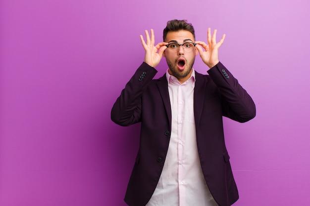 Joven hispano sintiéndose sorprendido, asombrado y sorprendido, sosteniendo gafas con una mirada asombrada e incrédula
