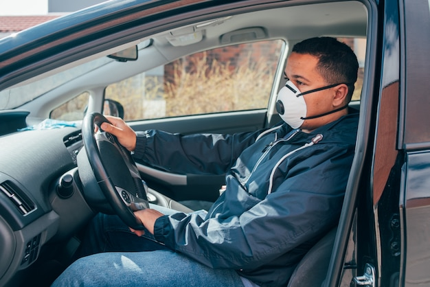 Joven hispano está solo en el auto con máscara protectora