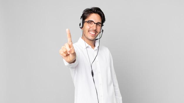 Joven hispano sonriendo con orgullo y confianza haciendo el número uno. concepto de telemarketer
